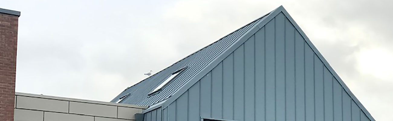 a zinc cladding roof installation by wellwood roofing solutions on the side of a commercial building